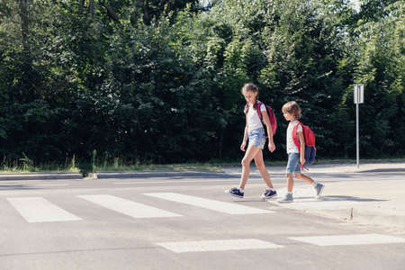 Fille et garçon avec des sacs à dos marchant sur le passage pour piétons de l'école