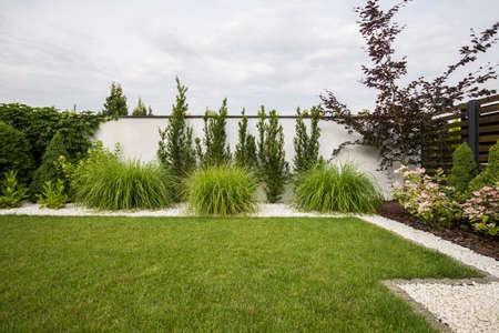 Grünes Gras, Blumen und Bäume auf der Terrasse mit Büschen und weißen Steinen