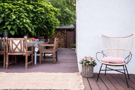 Rosa Blumen neben Sessel auf Holzterrasse mit Stühlen am Tisch neben Baum Standard-Bild