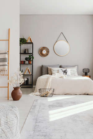 Vertical view of elegant ethno bedroom with king size bed, stylish carpet and round mirror on the wall, real photo with copy space Imagens - 110464630
