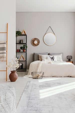 Vertikale Ansicht des eleganten Ethno-Schlafzimmers mit Kingsize-Bett, stilvollem Teppich und rundem Spiegel an der Wand, echtes Foto mit Kopierraum