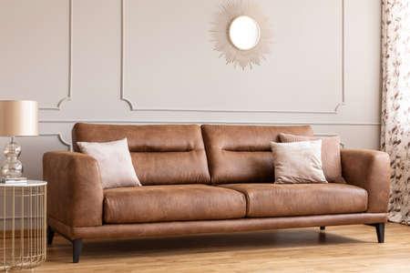 Espejo sobre el sofá de cuero con almohadas en el interior de la sala de estar gris con lámpara de oro en la mesa. Foto real