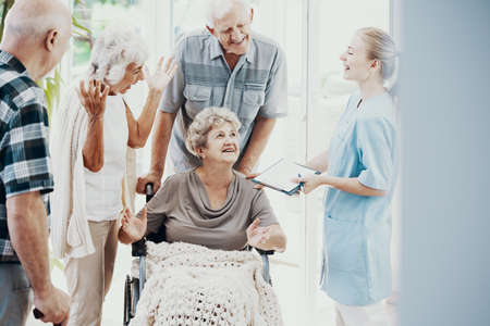 Smiling friends and nurse supporting paralyzed senior woman in the wheelchair Stock Photo