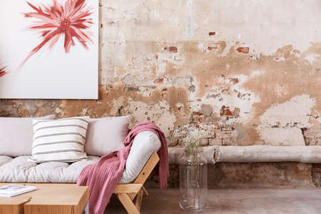 Pink blanket and pillows on wooden couch next to flowers in industrial flat interior with poster. Real photo