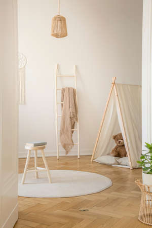 Vertical view of white scandinavian playroom with tent, teddy bear and wooden ladder with beige blanket, real photo