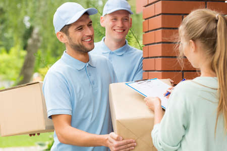 Two smiling couriers in blue uniforms and young women filling up delivery documents