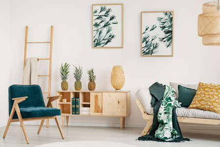 Stylish retro armchair next to wooden cabinet with book and three pineapples on top of it, graphics on the wall Stock Photo
