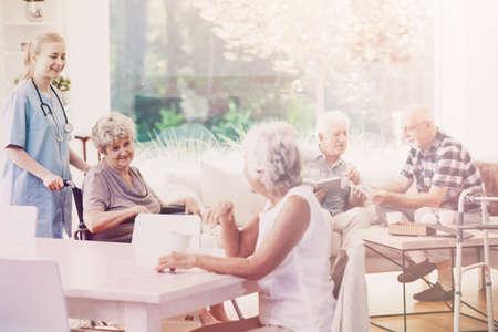 Happy nurse helping senior woman in the wheelchair next to smiling elderly people