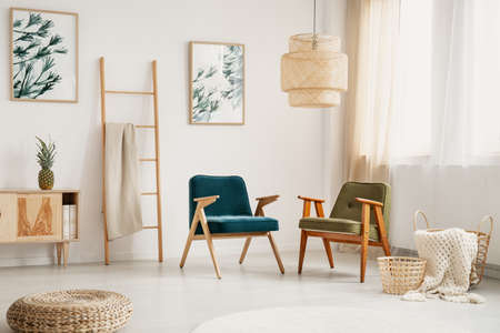 Two stylish retro armchairs in white and bright living room with furniture made of natural materials