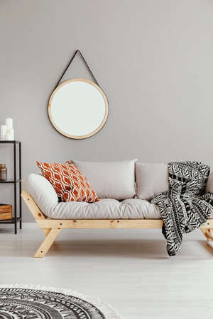 Mockup of round mirror above grey settee with patterned blanket in boho flat interior. Real photo