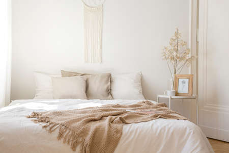 Kingsize bed met wit beddengoed, beige kussens en deken naast nachtkastje met bloem, koffiebeestje en print in frame, echte foto