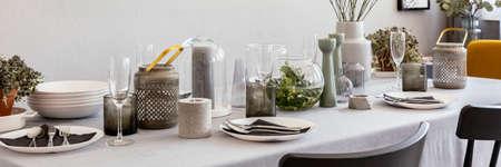 Panorama szary stół z kieliszkami do wina, świecami i zastawą stołową we wnętrzu jadalni. Prawdziwe zdjęcie