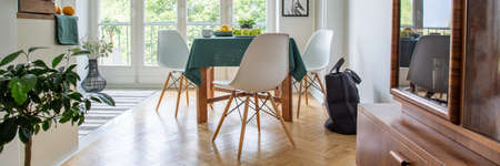 Three white wooden chairs by the table in vintage kitchen with terrace in elegant apartment, real photo Stock Photo
