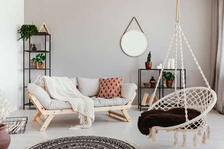 Hanging chair near grey wooden sofa in ethno living room interior with round mirror. Real photo