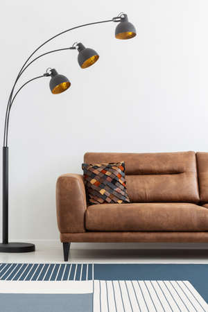 Modern lamp next to leather sofa in white living room interior with patterned carpet. Real photo