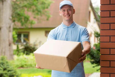 Gelukkige jonge koerier in blauw uniform met een pakket Stockfoto
