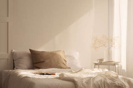 Linen sheets ion king size bed in minimal bedroom interior of stylish house, real photo with copy space on the empty wall