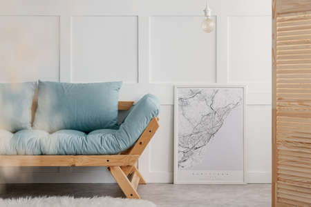 Blue sofa with pillows next to map in white frame in elegant living room interior of minimal house, real photo with copy space on the empty wall