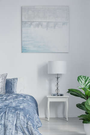 Lamp on white cabinet next to blue bed in bedroom interior with posters and plant. Real photo Stockfoto