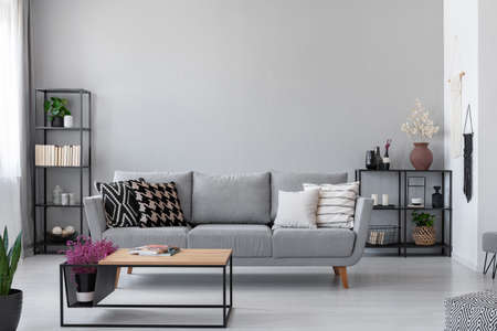 Copy space on the wall of scandinavian living room with modern couch, metal shelves and industrial coffee table, real photo