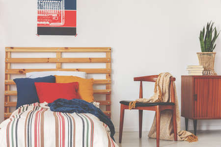 Blue, red and orange pillows on single bed with stripped duvet and wooden headboard in oldschool bedroom interior, real photo