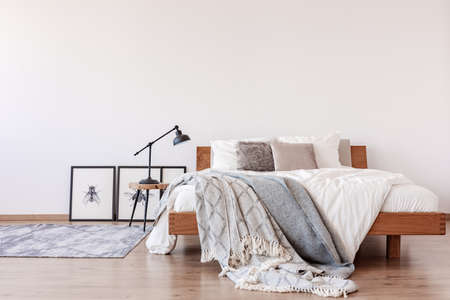 Comfortable king size bed with pillows and blankets in bright bedroom interior with rustic carpet on the floor, real photo with copy space Stockfoto