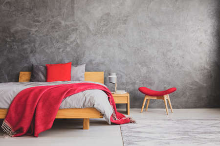 Red pillow and blanket on comfortable bed with grey bedding in simple bedroom with copy space on the empty concrete wall, real photo Stock Photo