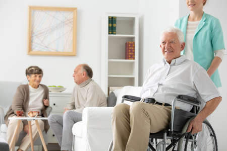 Friendly nurse in blue uniform supporting disabled elderly man on wheelchair in the nursing house