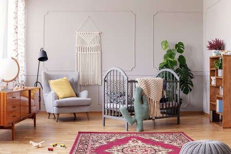 Cozy baby room with comfortable armchair with yellow pillow and grey wooden crib, real photo Stock Photo