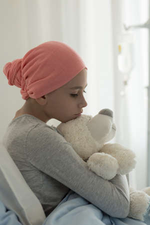 Vertical view of sick teenager girl in hospital bed after chemotherapy Stock fotó