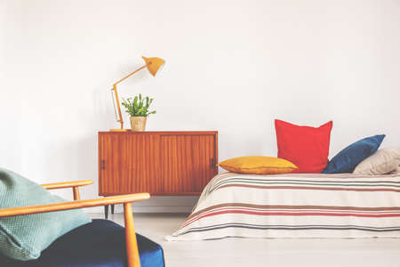 Hipster bedroom with vintage furniture and colorful bedding Stock Photo