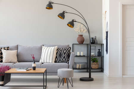 Black industrial lamp next to grey couch with patterned pillows, coffee table and pouf in monochromatic living room, real photo with copy space on the wall