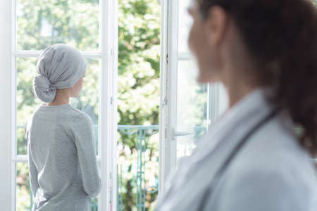 Sad girl with leukemia looking through the window in hospice, helpful doctor next to her