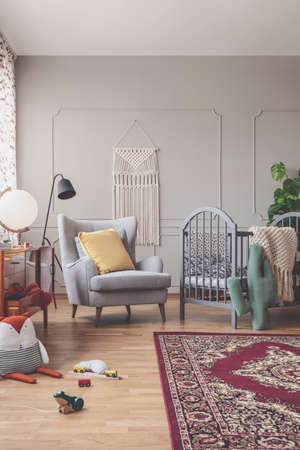 Vertical view of mid century baby room with rustic rug, comfortable grey armchair and wooden crib with patterned bedding Stock Photo