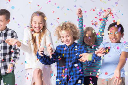Fröhlicher Junge viel Spaß während der Geburtstagsfeier mit lächelnden Freunden mit Konfetti