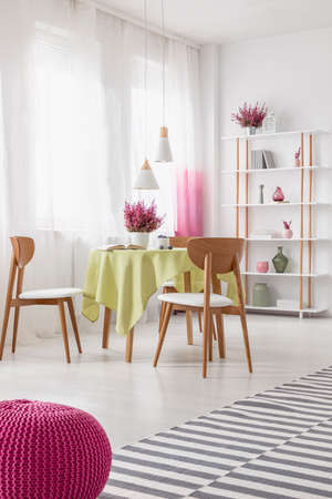 Real photo of bright dining room interior with table with cloth and heather, window with curtains and wooden rack with decor and books