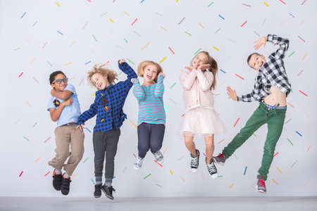 Happy multicultural group of kids jumping against colorful wallpaper Archivio Fotografico