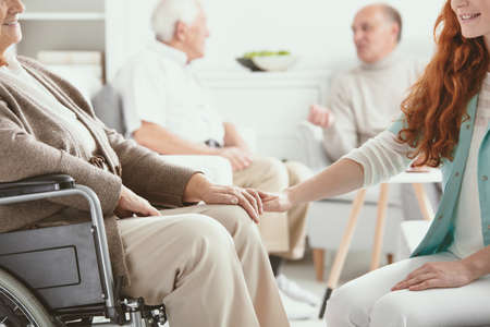 Friendly young nurse supporting paralyzed senior woman on wheelchair in nursing house Banque d'images - 110739276