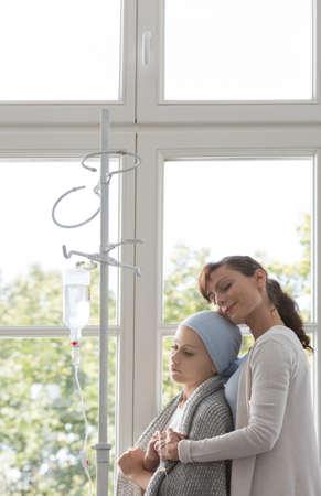 Smiling mother hugging sick daughter in medical center before cancer treatment Standard-Bild - 110739180