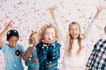 Glückliche multikulturelle Gruppe von Kindern, die während der Geburtstagsfeier mit Konfetti Spaß haben