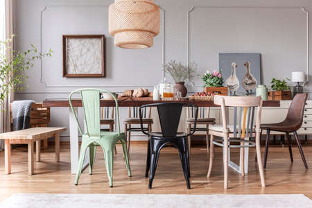 Real photo of a rustical dining room interior with a wicker lamp, table, chairs and plants Foto de archivo - 110642503