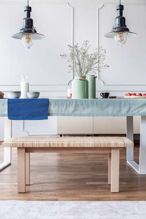 Bench and blue cloth on a table in a dining room interior. Real photo
