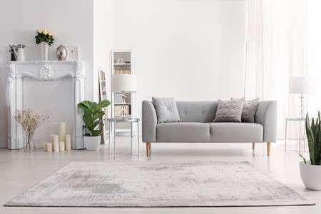 Planten en tapijt in wit woonkamer interieur met kaarsen naast grijze bank. echte foto