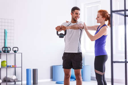 Smiling personal trainer and sportswoman working out with weight at gym Stok Fotoğraf