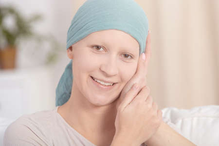 Woman with cancer smiling and being touched by someone