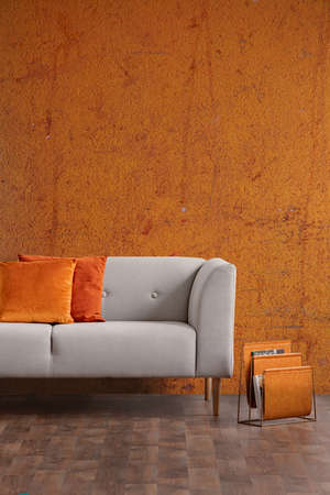 Wabi sabi living room interior with old orange wall and new stylish couch with pillows, real photo with copy space