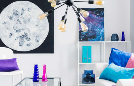 Moon and cosmos graphics on the wall of stylish white living room with colorful accessories, real photo