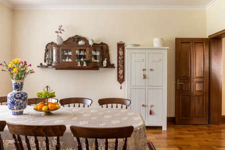 Wooden chairs at table with flowers in bright elegant dining room interior with door. Real photo