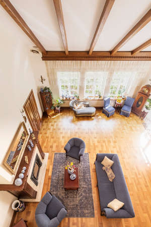 High angle on sofa and armchairs next to wooden table on carpet in classic house interior. Real photo