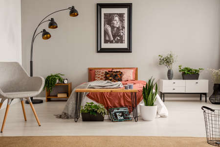 Stylish grey chair, black lamp, poster on the wall and king size bed with rust color bedding in bright bedroom of stylish flat, real photo with copy space on the grey wall Redakční